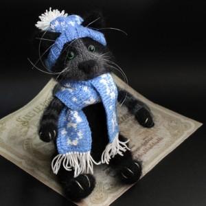 Фото Игрушка вязаная Чёрный кот в синем шарфе и шапке